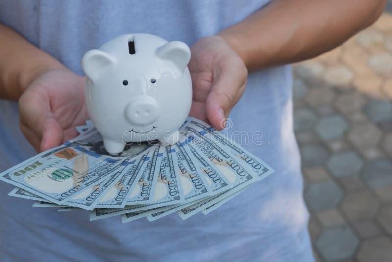 Asiatisk man som rymmer hundra dollarräkningar med samman med den vita spargrisen F?rm?gen och rikedombegrepp royaltyfri fotografi
