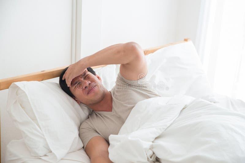 Asiatisk man som sover på sängen och handen på pannan royaltyfri bild