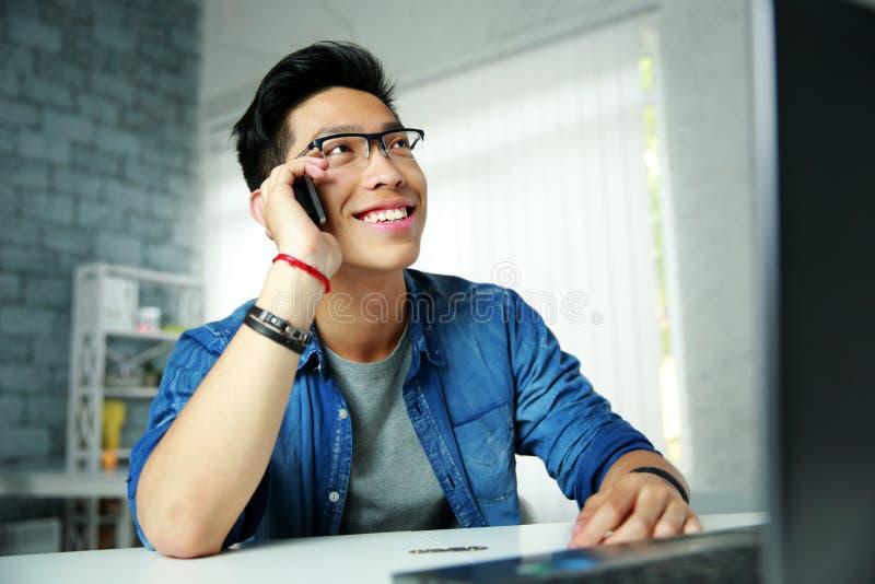 Asiatisk man som talar på telefonen på hans arbetsplats arkivfoto