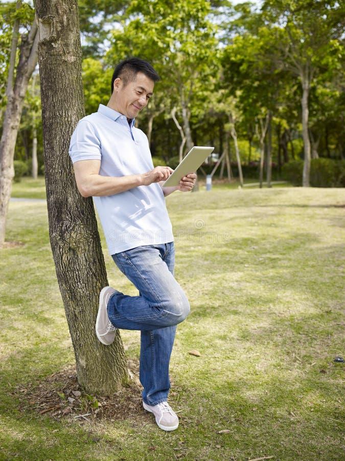 Asiatisk man som utomhus använder minnestavlan arkivbilder