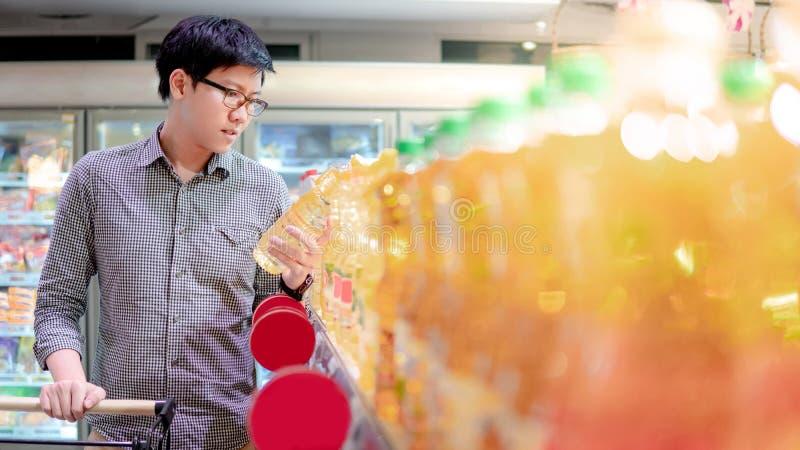 Asiatisk man som väljer grönsakolja i supermarket arkivfoto