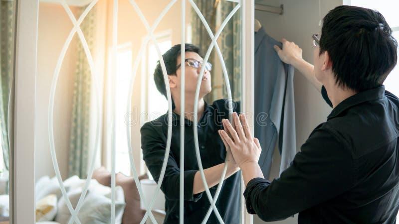 Asiatisk man som väljer skjortan i garderob arkivfoton