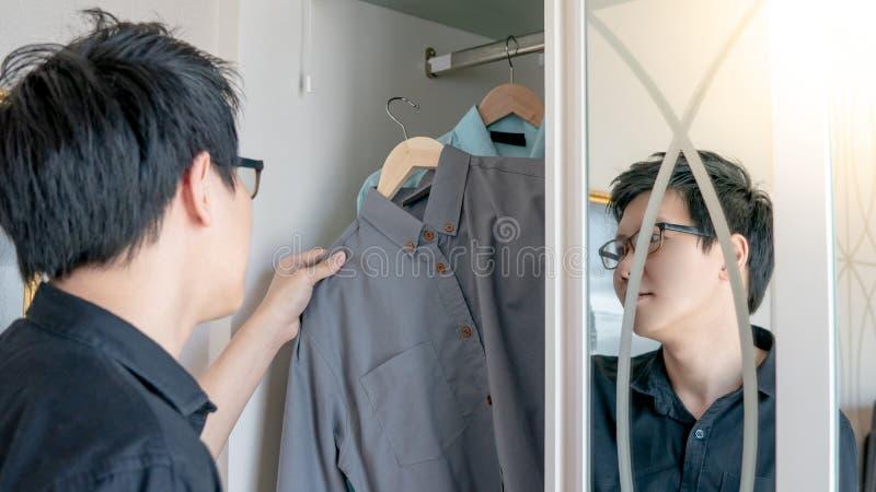 Asiatisk man som väljer skjortan i garderob fotografering för bildbyråer