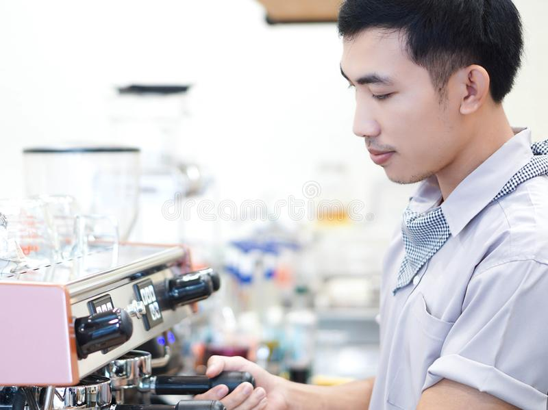 Asiatisk manbarista för Closeup som förbereder sig för framställning av kaffe på kafét med lycklig känsla arkivbilder