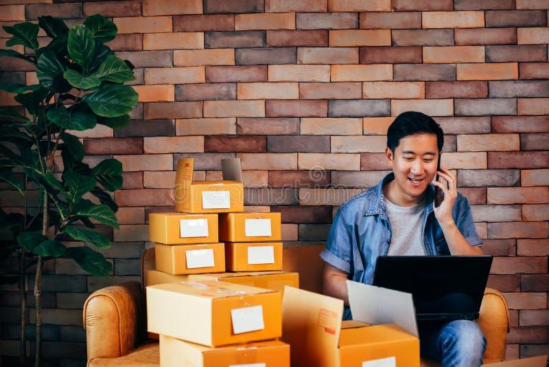 Asiatisk manlig affärsentreprenör som hemma använder bärbara datorn och telefonen med packar av askar royaltyfri fotografi