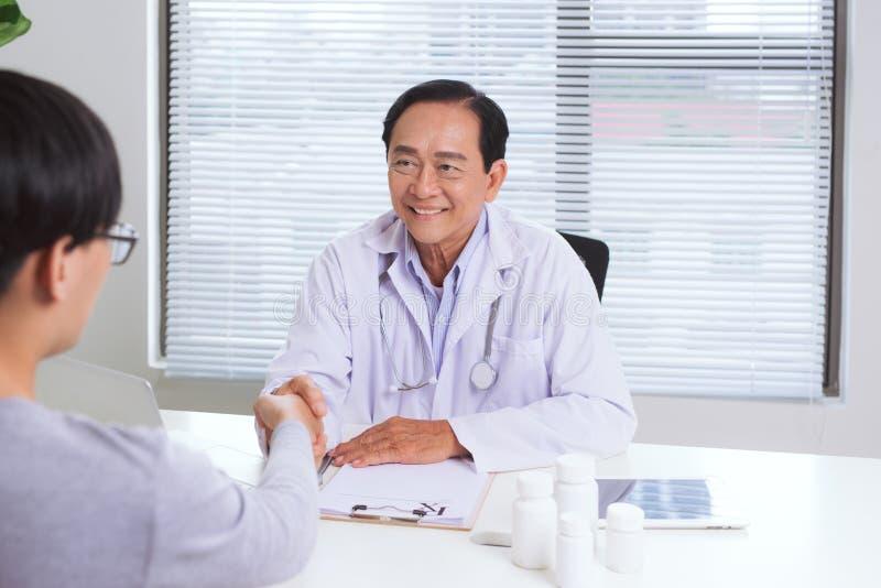 Asiatisk manlig doktor och patient i kontoret som skakar händer, healt royaltyfria bilder
