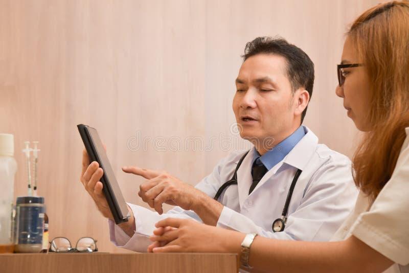 Asiatisk manlig doktor som använder den digitala minnestavladatoren arkivbild