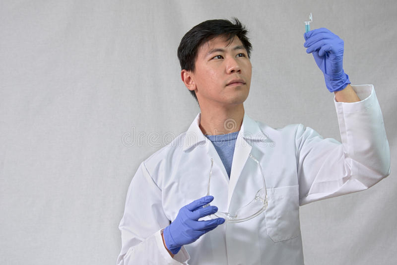 Asiatisk manlig forskare som ser den lilla provröret arkivbilder