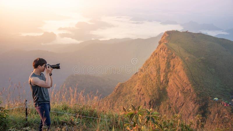 Asiatisk manlig fotograf som tar fotoet av landskap royaltyfri foto