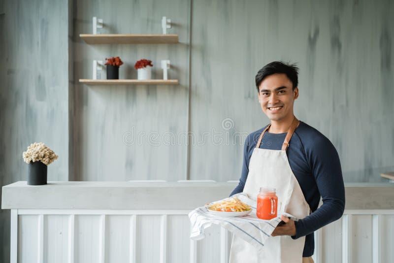Asiatisk manlig servitris som ser kameran och att le fotografering för bildbyråer