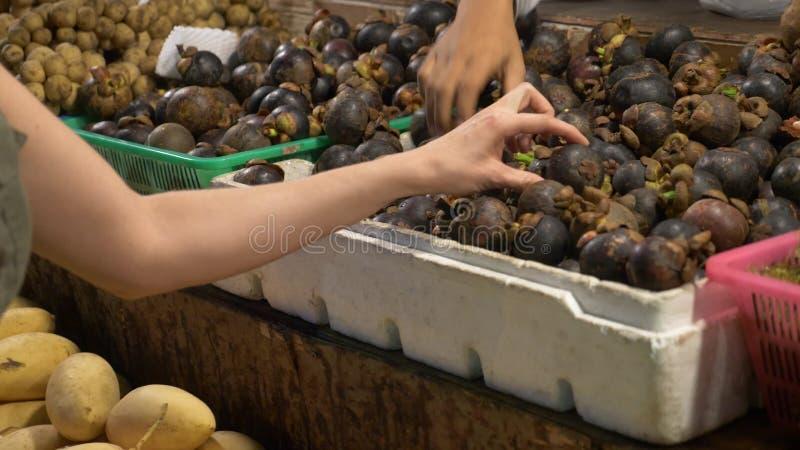 Asiatisk marknad, exotiska frukter en kvinna väljer frukt på en nattmarknad i Thailand royaltyfria bilder