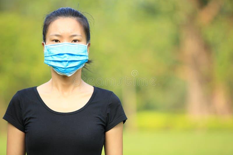 Asiatisk maskering för framsida för kvinnakläder i stad royaltyfri fotografi