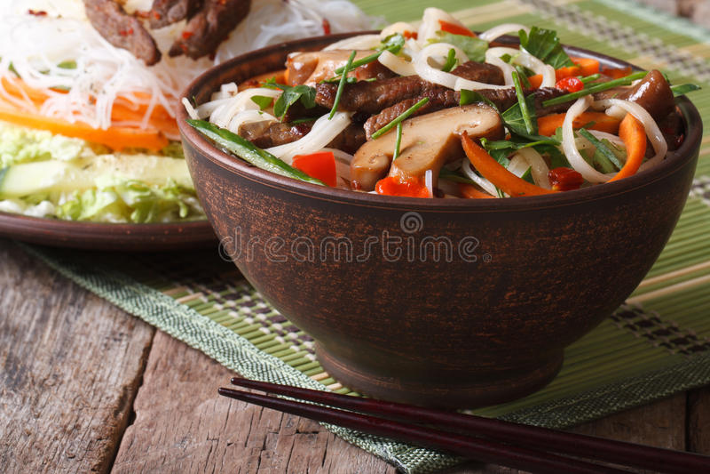 Asiatisk mat: risnudlar med shiitaken och grönsaker i en bunke royaltyfri foto