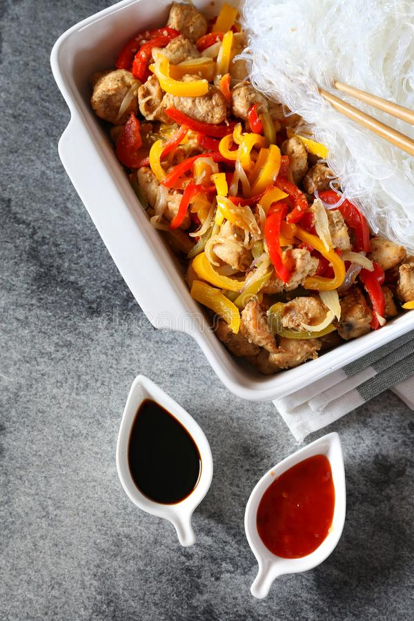 Asiatisk mat: stekt kyckling med tricolor spanska peppar och ris ve arkivbild