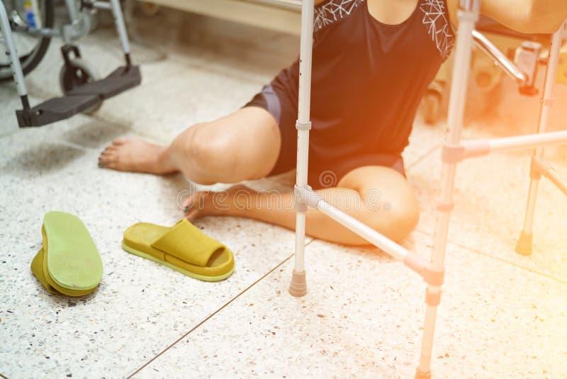 Asiatisk medelålders damkvinnapatient som faller i vardagsrum därför att hala yttersidor royaltyfri fotografi