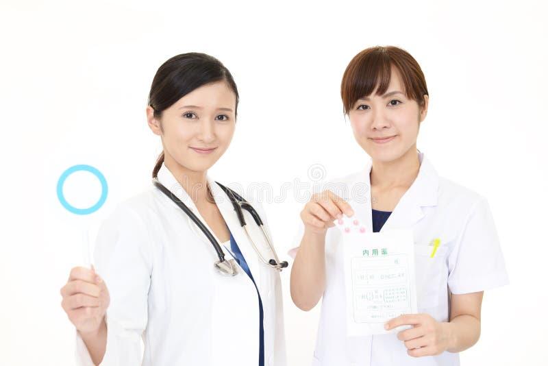 Asiatisk medicinsk personal med ett jatecken royaltyfri foto
