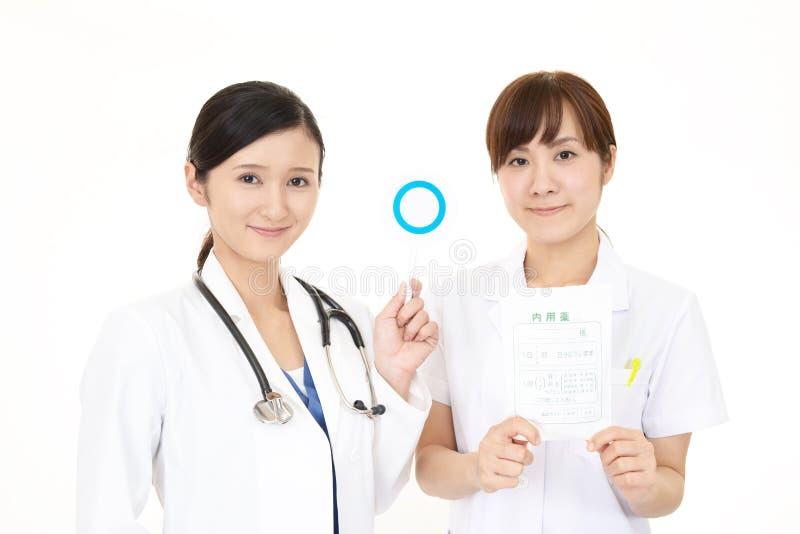 Asiatisk medicinsk personal med ett jatecken royaltyfri bild