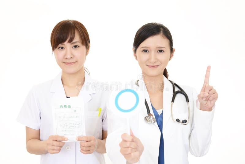 Asiatisk medicinsk personal med ett jatecken arkivbilder