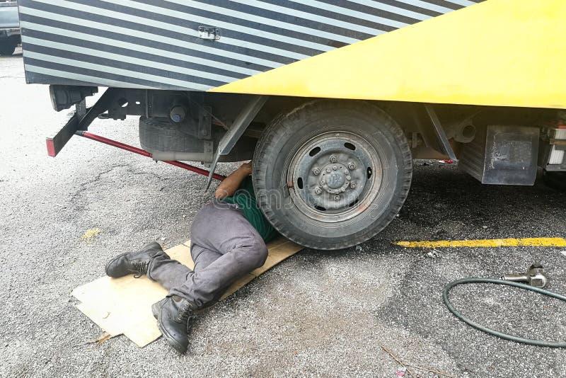 Asiatisk mekaniker under lastbilen som reparerar den smutsiga fetthaltiga motorn med pr royaltyfri foto