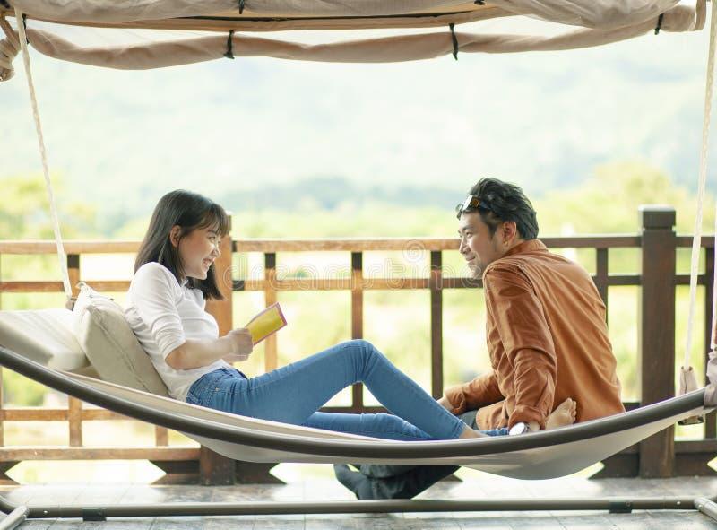 Asiatisk mer ung man och kvinna som ler framsidalyckasinnesrörelse som kopplar av på vagga royaltyfri foto