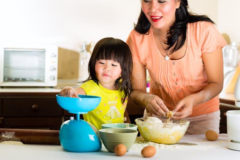 Asiatisk moder och dotter hemma i kök royaltyfria bilder