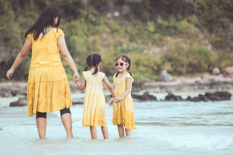Asiatisk moder och dotter som går och spelar på stranden royaltyfri bild