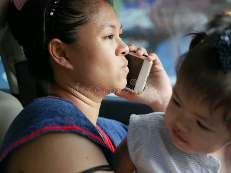Asiatisk moder som gör uncomfortably en påringning, medan handla med hennes dotter i en körande bil arkivfoton