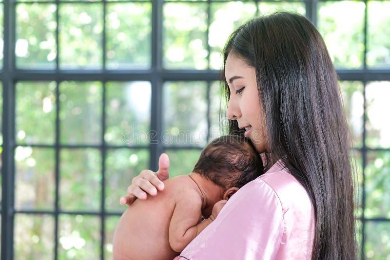 Asiatisk moder som rymmer en 1 5-månad-gammalt barn som lutar över hennes skuldra royaltyfria foton
