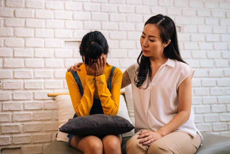 Asiatisk moder som tröstar gråta den tonårs- dottern i bedrövligt, stressat, deprimerat ledset tillstånd av meningen fotografering för bildbyråer