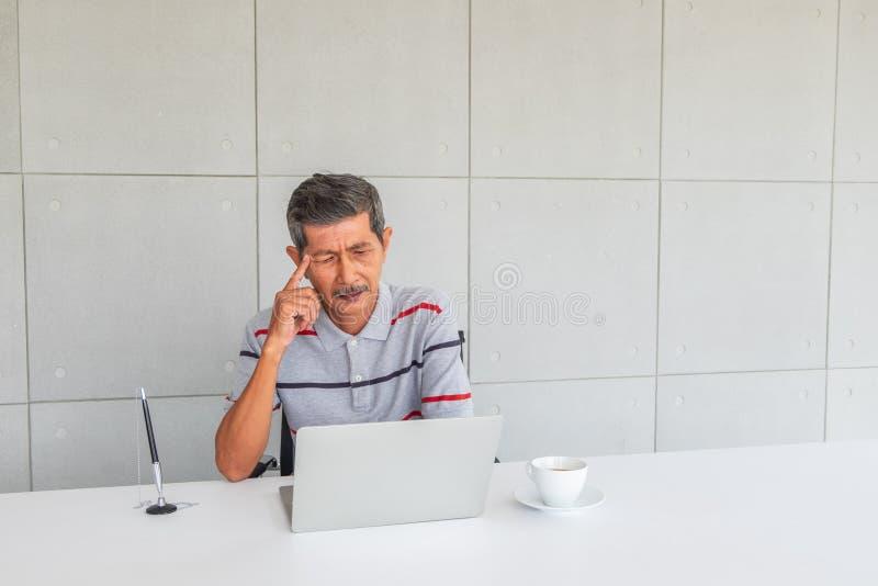 Asiatisk mogen affärsman som tänker något framdel p? skrivbordet arkivbild