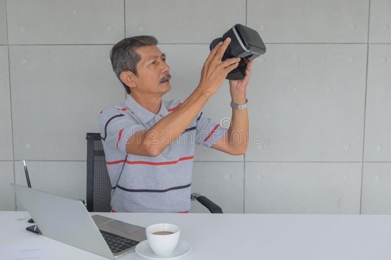 Asiatisk mogen man som rymmer VR-exponeringsglas för ny modern teknologi för provning arkivbild
