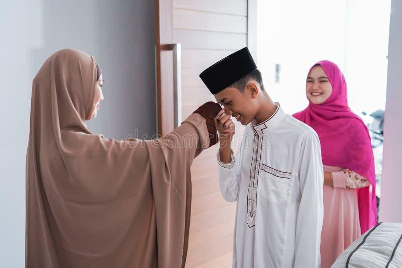 Asiatisk muslim förälderskakahand i idulfitrieid mubarak arkivbilder