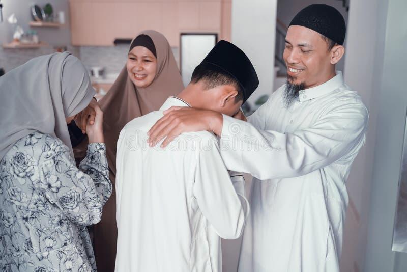 Asiatisk muslim f?r?lderskakahand i idulfitrieid mubarak royaltyfri fotografi