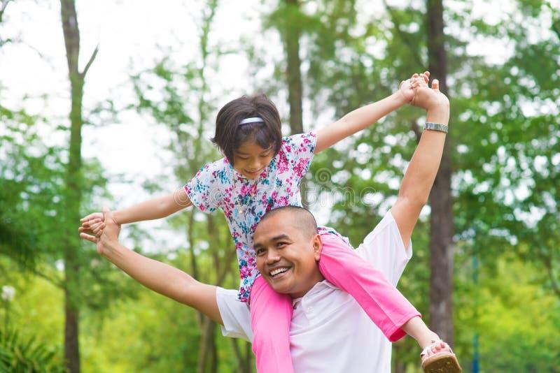 Asiatisk muslimsk fader och dotter på ryggen arkivfoton