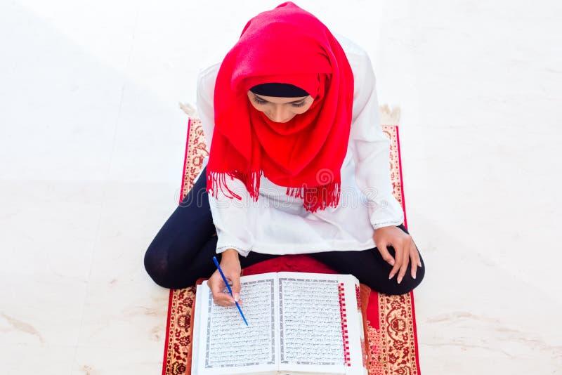 Asiatisk muslimsk kvinna som studerar Koranen eller Quran royaltyfri bild