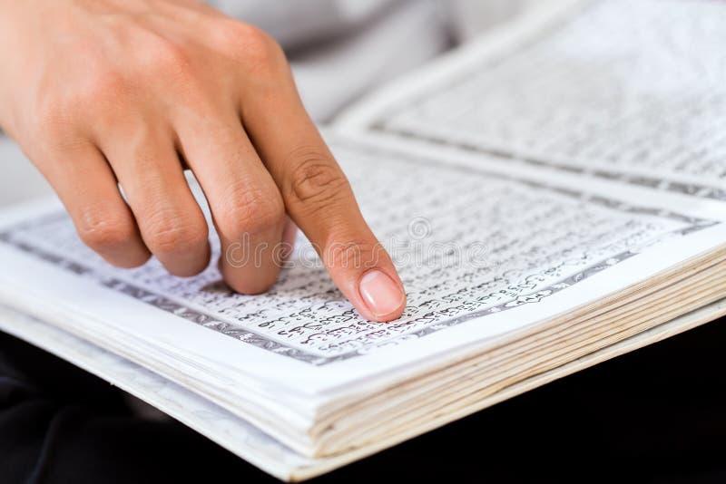 Asiatisk muslimsk man som studerar Koranen eller Quran royaltyfri foto