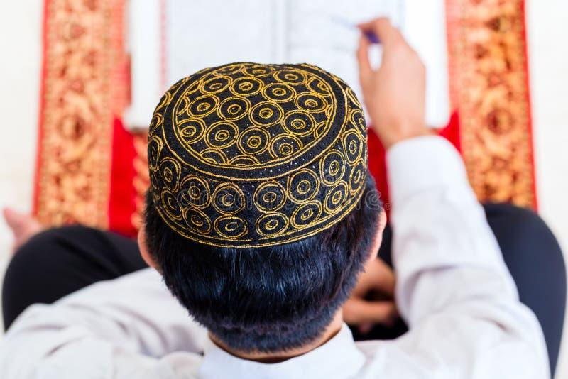 Asiatisk muslimsk man som studerar Koranen eller Quran arkivbild