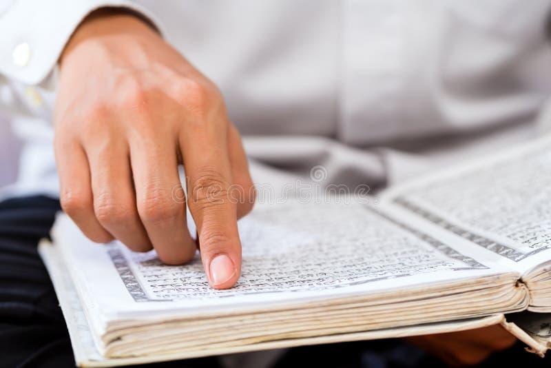Asiatisk muslimsk man som studerar Koranen eller Quran royaltyfria bilder