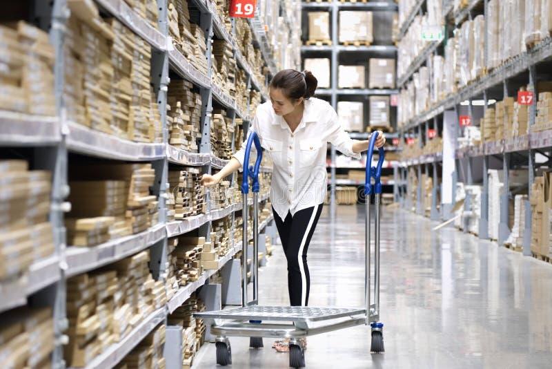 Asiatisk n?tt kund som s?ker produkter i lagerlager Flickan som anv?nder hennes handpunkt till etiketten f?r att kontrollera numr royaltyfria foton
