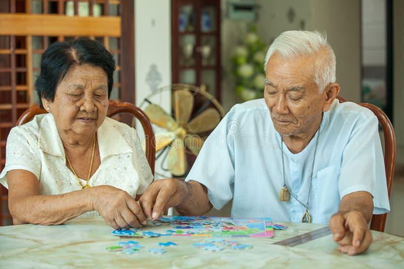 Asiatisk parpensionär som spelar med ett pussel arkivbilder