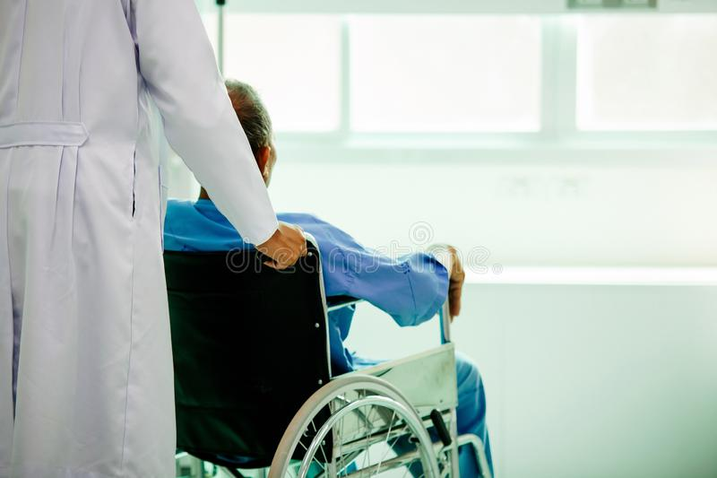 Asiatisk patient i rullstolsammanträde i sjukhus med asiatisk docto royaltyfria bilder