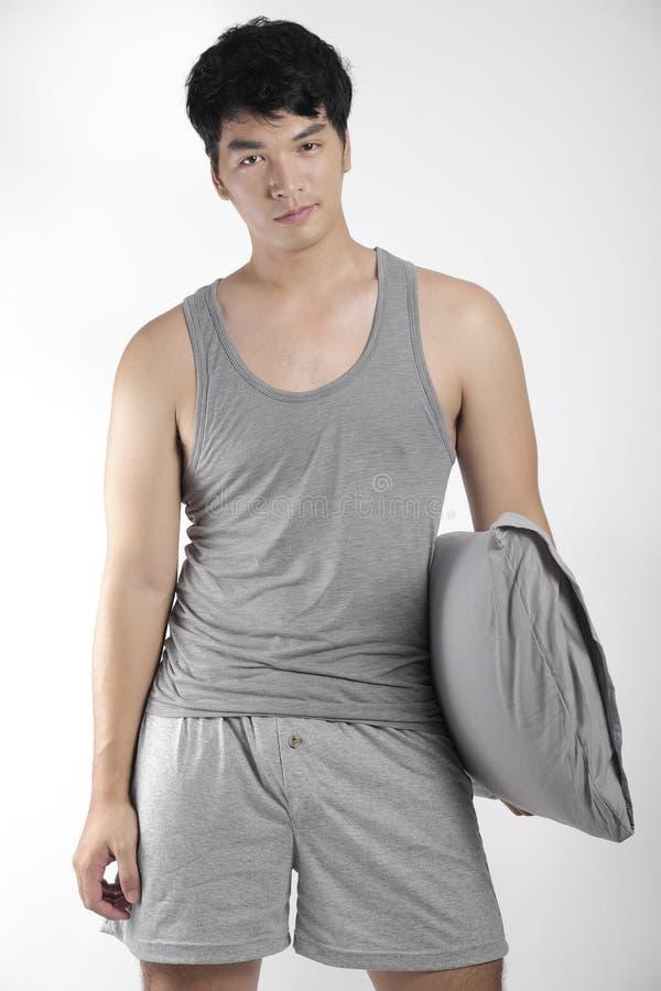 Asiatisk pojke i grå pyjamas med en kudde royaltyfria foton