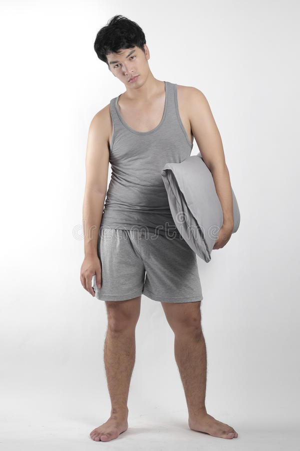Asiatisk pojke i grå pyjamas med en kudde arkivfoto