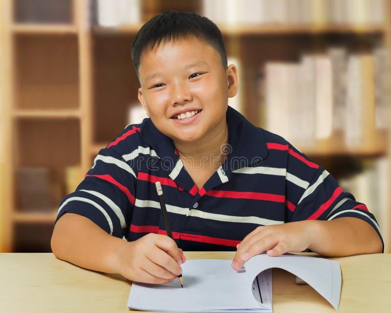 Asiatisk pojke som är lycklig med hans läxa arkivfoto