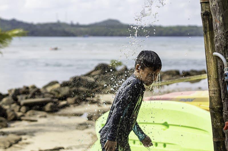 Asiatisk pojke som bär ett baddräkt- och duschbakgrundshav royaltyfria bilder