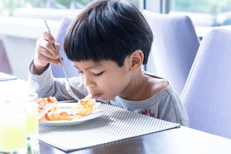 Asiatisk pojke som har frukosten i kafé royaltyfri fotografi