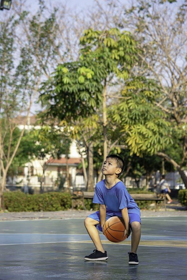 Asiatisk pojke som rymmer oskarpa träd för en basketbollbakgrund royaltyfri bild