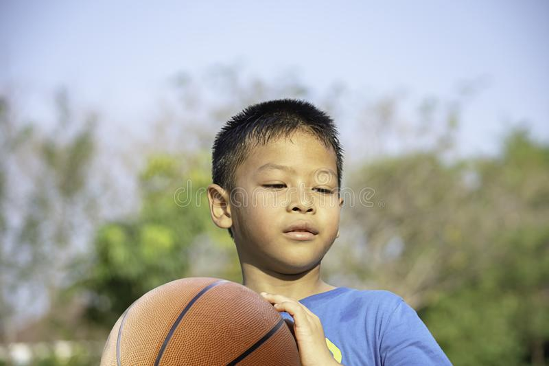 Asiatisk pojke som rymmer oskarpa träd för en basketbollbakgrund fotografering för bildbyråer