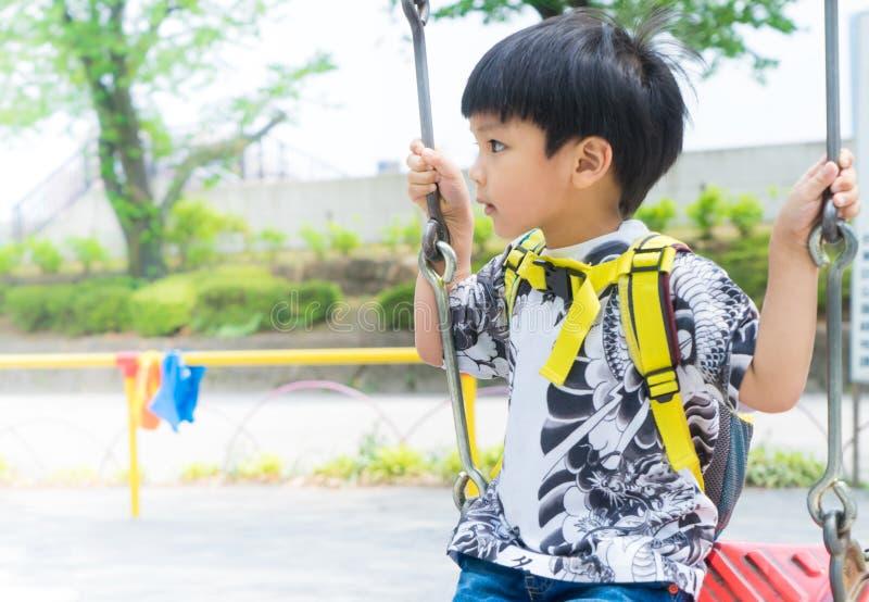 Asiatisk pojke som spelar på lekplatsgungan royaltyfri fotografi