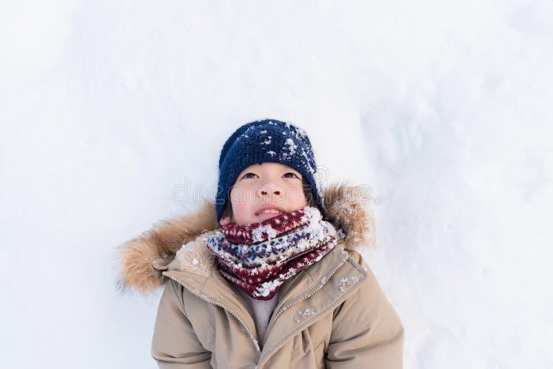 Asiatisk pojke som spelar snö royaltyfri bild